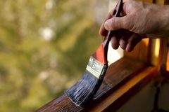 Fragment of a man`s hand with a brush. A man processes varnish of a window transom. A concept of repair royalty free stock photography