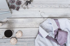 Fragment of a men`s shirt with a tie on a hanger, crackers, coff. Ee cup on a wooden painted surface. The pastel colors Royalty Free Stock Photos