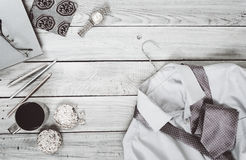 Fragment of a men`s shirt with a tie on a hanger, diary, coffee. Cup on a wooden painted surface. Black and white photo Stock Photography