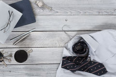Fragment of a men`s shirt with a tie on a hanger, diary, coffee Stock Photo