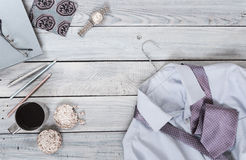 Fragment of a men`s shirt with a tie on a hanger, diary, coffee. Cup on a wooden painted surface. The pastel colors Royalty Free Stock Photography