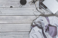Fragment of a men`s shirt with a tie on a hanger, diary, coffee. Cup on a wooden painted surface. The pastel colors Royalty Free Stock Image