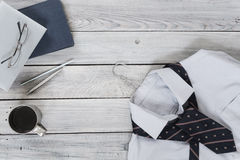 Fragment of a men`s shirt with a tie on a hanger, diary, coffee Royalty Free Stock Image