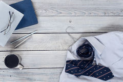 Fragment of a men`s shirt with a tie on a hanger, diary, coffee. Cup on a wooden painted surface. The pastel colors Royalty Free Stock Images