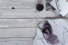 Fragment of a men`s shirt with a tie on a hanger, diary, coffee. Cup on a wooden painted surface. The pastel colors Stock Photography