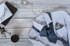 Fragment of a men`s shirt with a tie on a hanger, diary, coffee. Cup on a wooden painted surface. The pastel colors Stock Images