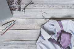 Fragment of a men`s shirt with a tie on a hanger and diary on a. Wooden painted surface. The pastel colors Royalty Free Stock Photography