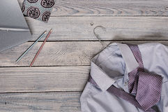 Fragment of a men`s shirt with a tie on a hanger and diary on a. Wooden painted surface. The pastel colors Royalty Free Stock Images