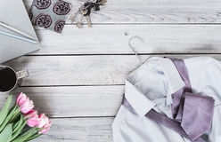 Fragment of a men`s shirt with a tie on a hanger, tulips, coffee. Cup on a wooden painted surface. The pastel colors Stock Images