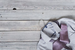 Fragment of a men`s shirt with a tie on a hanger on a wooden pai. Nted surface. The pastel colors Royalty Free Stock Image