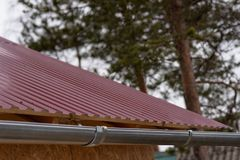 Fragment of the metal roof of the house. Red roof stock photography