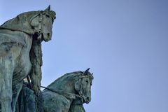 Side view on statue horses of  the chieftains of the Magyars against a blue sky. Fragment of the Millennium Monument on the Heroes stock photography