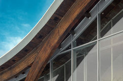 Fragment of modern building with structural glass wall. Detail of building facade. Interfacing of wooden structure glued elements. Glulam beams detail Royalty Free Stock Photos