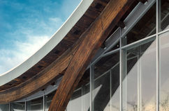 Fragment of modern building with structural glass wall. Detail of building facade. Interfacing of wooden structure glued elements. Glulam beams detail Stock Image
