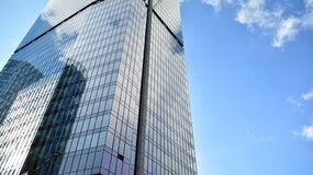 Blue curtain wall made of toned glass and steel constructions under blue sky.