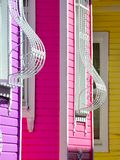 Fragment of a multicolor facade of the house with curved bars on the windows stock image