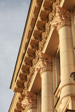 Fragment of neoclassic building with columns and fine capitals. Fragment of classic or neoclassic building with columns and fine capitals, illuminated with warm Stock Photography
