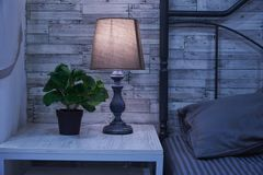 Free Fragment Of A Bedroom With A Bedside Table And A Bed. A Table Lamp And A Houseplant Are On The Nightstand Royalty Free Stock Images - 164350049