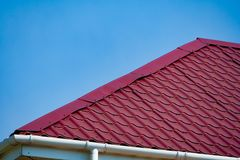 Free Fragment Of A Purple Metal Tile Roof A Background Of Blue Sky Stock Images - 135945654
