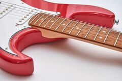 Fragment Of A Red Electric Guitar On A White Background. Part Of The Guitar. Music Object Royalty Free Stock Photos
