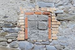 Fragment of an old brick wall with cultural layers and a window frame element, background texture. Royalty Free Stock Image
