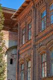 Fragment of an old building of red brick, windows with wooden fr. An old abandoned house with a ruined roof and overgrown courtyard, poverty and discouragement Royalty Free Stock Photography