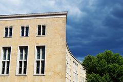Fragment of old building with yellow facade. Against blue sky and green tree with copy space for text on sky in summer day in Berlin stock photo