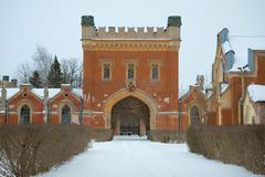 Fragment of a old complex of Imperial Gothic stables in the cloudy February afternoon. Peterhof Royalty Free Stock Image