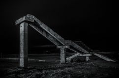 Fragment of the old conrete bridge near seaside of Nabran. North of Azerbaijan. Caspian Sea at night time with freezelight on it w. Ith different colors. View stock image