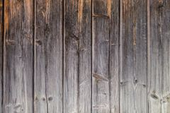 Fragment of the old country house of natural wooden timbers without coloring. Gray-brown wooden background. vertical wooden stripe. Fragment of the old country royalty free stock image