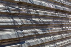 Fragment of an old fence of an abandoned construction site, made of metal sheets. Sunlit fragment of the fence. Metal corrugated sheet royalty free stock images