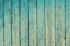Fragment of an old fence. Cracked cyan paint texture. Shabby aquamarine paint wooden planks background. Royalty Free Stock Photos