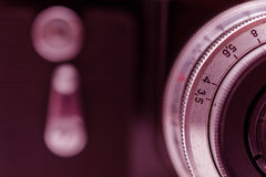 Fragment old film camera with lens.  and  self-timer button. Vintage photo.Toning. Royalty Free Stock Photos