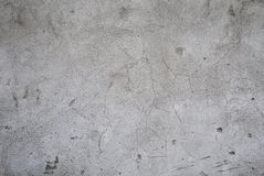 Fragment of an old gray concrete wall with cracks and broken pieces closeup. Background image. royalty free stock photo