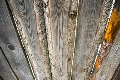 Fragment of an old grey rough-hewn fence. Wooden texture. Texture, background.Old unpainted wood surface. Wooden plank royalty free stock photos
