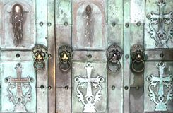 Fragment of old iron church door. With icons, crosses and door handles in shape of lion stock photos