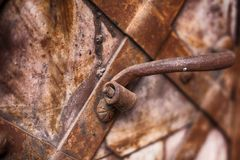 Fragment of the old iron door. Forged handle on the background of metal doors. Fragment of the old iron door Stock Image