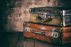 Fragment of old leather suitcases on wooden table. Processing in vintage style. The concept of travel Royalty Free Stock Image