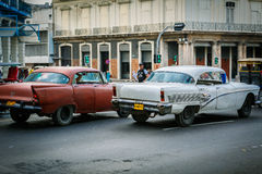 Fragment of old retro vintage classic old cars driving on authentic Cuban Havana city streets toward traffic lights Royalty Free Stock Photo