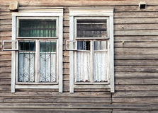 Fragment of old rural wooden wall with windows. Fragment of old rural Russian wooden wall with two windows Stock Photography