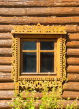 Fragment of old Russian architecture. Window decorated with wood carvings on the background log wall farmhouse Royalty Free Stock Image