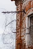 Fragment of the old Russian prison building: window with barbed wire-vertical photo. Fragment of the wall of an old Russian prison: a window with barbed wire royalty free stock images
