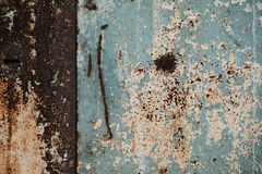 A fragment of an old rusty door. Cracked paint on rusty doors Royalty Free Stock Photography