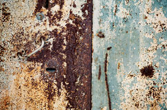 A fragment of an old rusty door. Cracked paint on rusty doors Royalty Free Stock Images
