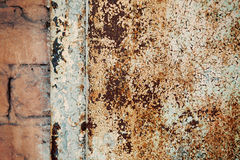 A fragment of an old rusty door. Cracked paint on rusty doors Stock Image