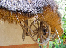 Fragment of an old thatched roof and under it the wooden wheel. Fragment of an old roof made of wheaten straw and under it the old wooden spoked cartwheel in the Stock Image