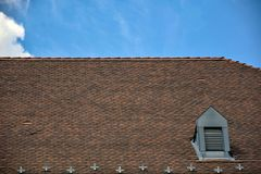 Fragment of the old tiled roof against the blue sky with clouds, architectural details of an old building royalty free stock photos