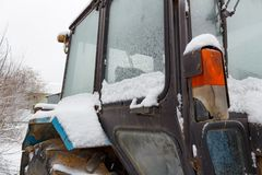 Fragment of the old tractor cab covered with snow closeup. Side view stock photo