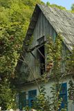 Fragment of the old village house. Of traditional architecture in the overgrown garden Royalty Free Stock Image