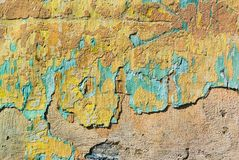 Fragment of the old wall with many layers of plaster of different colors, which partially crumbled under the influence of time royalty free stock photography